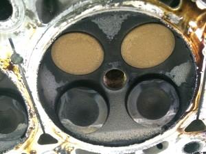 На фото впускные и выпускные клапана, верхние выпускные, нижние впускные , впускные клапана находятся в открытом состоянии ,клапаны погнуты, причина потери компрессии, также видны следы ударов о поршни.